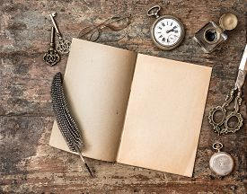 stock photo of inkwells  - Open book and vintage writing on wooden table - JPG