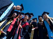 stock photo of graduation hat  - high school students graduates tossing up hats over blue sky - JPG