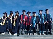 picture of graduation  - young graduates students group  standing in front of university building on graduation day - JPG