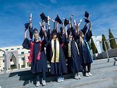 image of graduation hat  - high school students graduates tossing up hats over blue sky - JPG