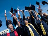 foto of graduation hat  - high school students graduates tossing up hats over blue sky - JPG
