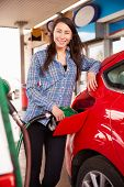 picture of petrol  - Woman refuelling a car at a petrol station - JPG