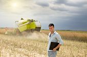 pic of combine  - Young attractive businessman standing in the field combine harvester in background - JPG