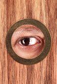 stock photo of peep hole  - Eye is looking through peephole - JPG