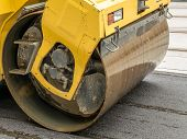 stock photo of heavy equipment operator  - Closeup of yellow road roller smoothing out fresh asphalt layer - JPG