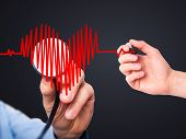 stock photo of heart surgery  - Closeup portrait doctor hand listening to heart beat in heart shape with stethoscope - JPG