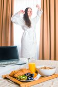 pic of bed breakfast  - Breakfast in bed and stretches himself a woman in a bathrobe - JPG