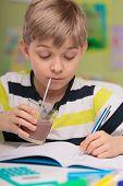 stock photo of homework  - Cute child drinking chocolate milk during homework - JPG