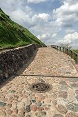 stock photo of cobblestone  - Cobblestone road up the hill on which stands an ancient castle - JPG
