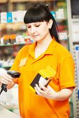 picture of cashiers  - seller cashier with bar code scanner scanning lamp at store - JPG