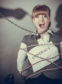 picture of scared  - Scared businesswoman bound by contract terms and conditions - JPG