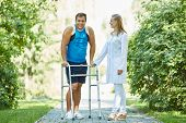 image of take responsibility  - Female clinician and young man with walker taking walk in park - JPG