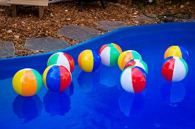 image of pool ball  - Colorful beach balls floating in pool.
