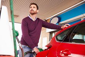 stock photo of petrol  - Man refuelling a car at a petrol station - JPG