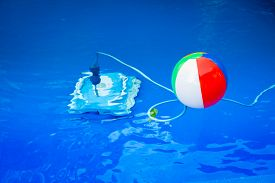 stock photo of pool ball  - Colorful beach ball floating in pool and next to him underwater a cleaning robot - JPG