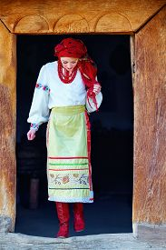 picture of national costume  - young ukrainian girl dressed in national costume walking out from house - JPG