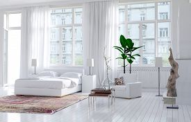 pic of high-rise  - Modern monochromatic bedroom interior in an apartment with large view windows and a double bed alongside an exterior door - JPG