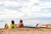 Couple surfers relaxing after surfing on hawaiian beach. Two people lying down on sand beach at suns poster