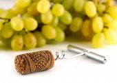 Corkscrew with wine cork and white grapes background