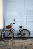 stock photo of cobblestone  - Bicycle with basket leaning against light blue door - JPG