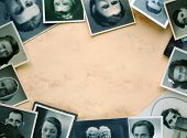 Eyes of old times. Ancient, worn, spotted and grainy photographs as frame on yellowish background