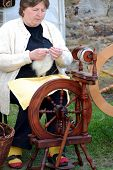 RATIBORICE, CZECH REPUBLIC - APRIL 24:  Older woman spinning wool on traditional spinning wheel - Th