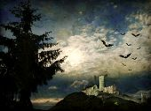 Mysterious dark scene with castle ruin, bats and big tree in moonlight
