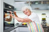 Постер, плакат: Senior woman cooking in the kitchen eating and cooking healthy for her family putting some potate