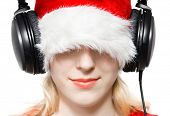 Young woman in santa hat listening music. Isolated on white.
