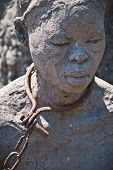 stock photo of slave  - Statue of a woman in slavery posed in Stone Town Zanzibar where once was placed the slave market - JPG