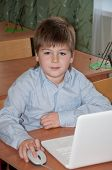 Schoolboy At His Desk With A Laptop In The Class Of  School