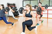 Determined Young Woman Doing Barbell Lunges With Friends In Health Club poster
