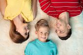 Little Boy With Mother And Father Lying On Fuzzy Rug, Top View poster