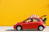 Authentic Santa Claus Driving Red Car With Gift Boxes And Christmas Tree, View From Outside poster