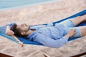 Young Man Resting In Hammock At Seaside. Summer Vacation poster