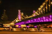 Motion Blurred Image Of Riding Cyclists Silhouettes On A Bright Bridge Background, City Night Illumi poster