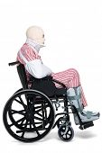 Photo of a man with various injuries wearing striped pyjames and sitting in a wheelchair.
