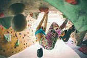 Strength And Endurance Training. The Climber Trains On The Climbing Wall. A Woman Trains To Climb On poster