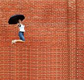 Lady jumping with umbrella high into air.