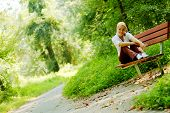 Pretty young girl sitting on a bench in the forest.