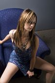 pic of risque  - sultry brunette in sexy dress rising out of armchair - JPG
