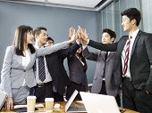Team Of Asian Business People Men And Women Putting Hands Together To Show Determination And Unity. poster