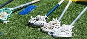 Four High School Boys Lacrosse Sticks Are Laying Down On A Green Turf Field. poster