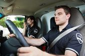 Portrait of EMS worker driving ambulance while team member talks with dispatcher