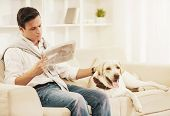 Young Man Sitting On White Sofa With Dog At Home. Reading Newspaper. Rest At Home. Relaxation Concep poster