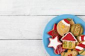 Top View Of A Plate Of Nicely Decorated Christmas Cookies On White Wooden Background. Selective Focu poster