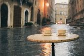 Rainy Day In Old European City, Wet Cafe Table With Two Cups Of Coffee poster
