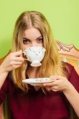 Fashionable Woman Drinking Cup Of Coffee Sitting On Vintage Sofa. Young Girl With Hot Energizing Bev poster