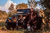 Hunter In Elegant Clothes Standing Together With His Beagle Dog Near A Retro Military Car In A Fores poster