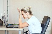 Beautiful Blonde Woman Working On Laptop At Home. She Is Thoughtful And Focused On Work. Freelance,  poster
